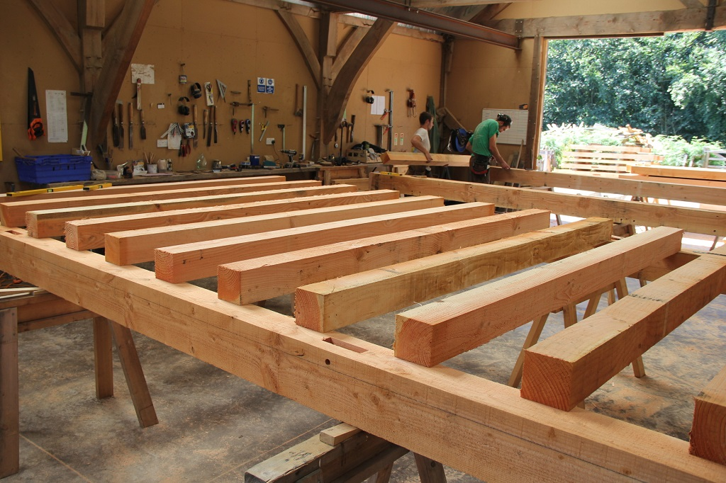 The douglas fir frame has a fully joisted floor. Here the joists are laid up on the floor beams ready for scribing